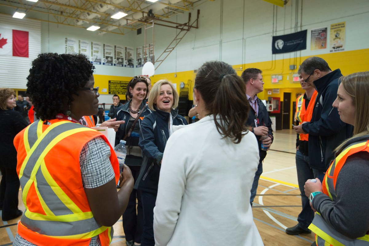 Premier Rachel Notley and Municipal Affairs Minister Danielle Larivee chat with volunteers at an information centre in Fort McMurray for returning residents on the first day they are allowed back into the city, June 1, 2016, after the mandatory evacuation in early May due to a massive wildfire. (photography by Chris Schwarz/Government of Alberta)