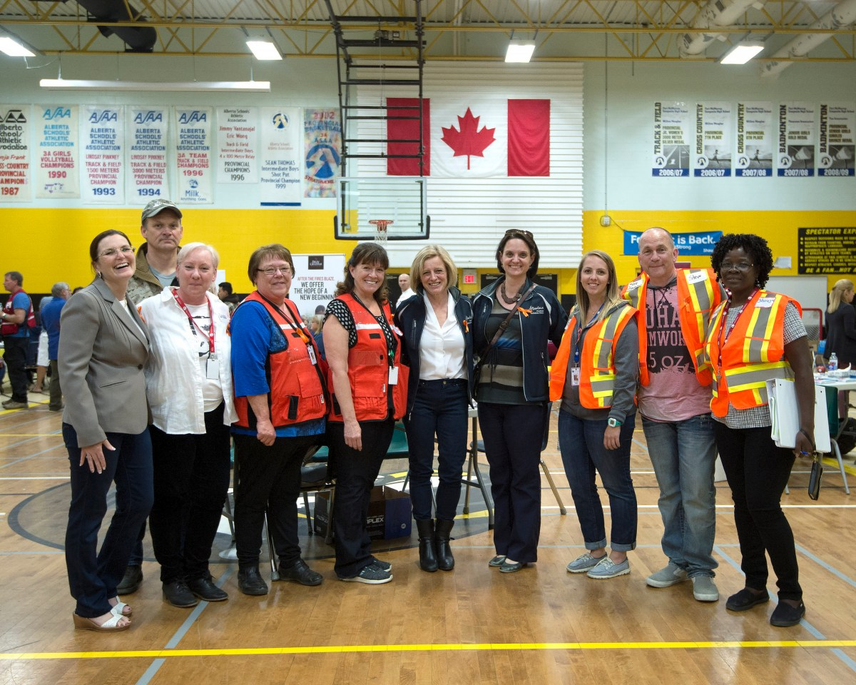 Premier Rachel Notley, Municipal Affairs Minister Danielle Larivee, and Mayor Melissa Blake with volunteers at an information centre in Fort McMurray.(photography by Chris Schwarz/Government of Alberta)