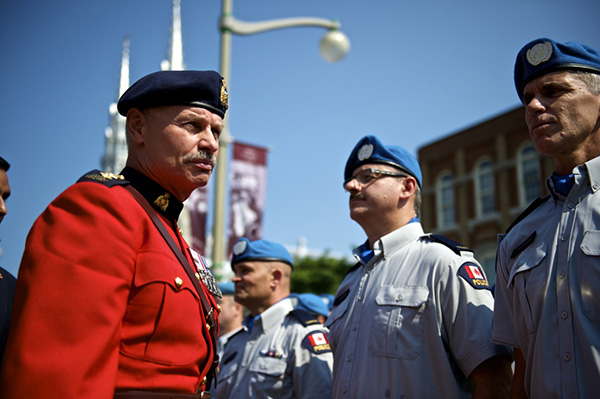 Chief Superintendent Marion Lamothe (left) reviews members of the police troop about to deploy to Haiti during a previous year's ceremony, including (from left to right) Montreal Police Cst. Roger Levesque, Sûreté du Québec Cst. Alain Pelletier, and Montreal Police Cst. Louis Raymond.