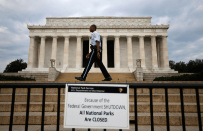 A National Parks policeman walks past a sign after the Lincoln Memorial was sealed off from visitors in Washington, October 1, 2013. The U.S. government began a partial shutdown on Tuesday for the first time in 17 years, potentially putting up to 1 million workers on unpaid leave, closing national parks and stalling medical research projects.