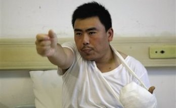 Officer Zhang points his gun at the burrning man