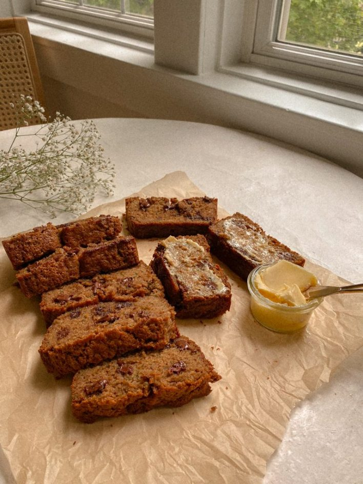 zucchini bread slices on brown parchment paper with small bowl of butter and white flowers