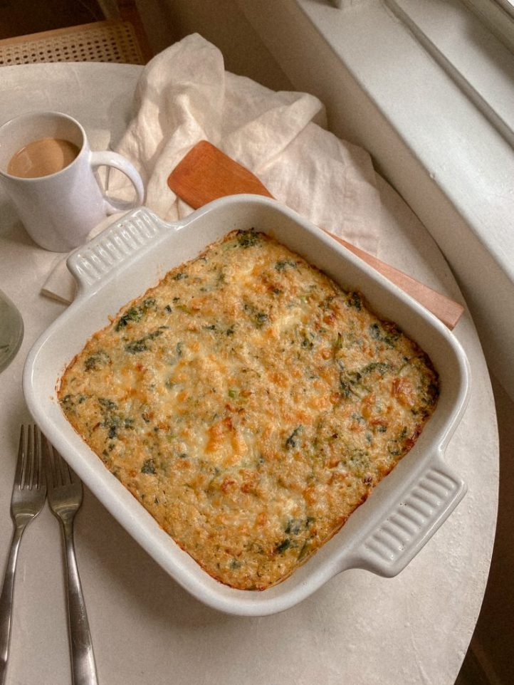broccoli cheddar quinoa breakfast bake in a white baking dish with a wooden spoon and mug of coffee