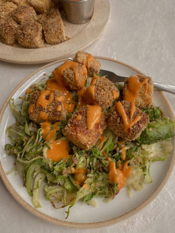 crispy baked tofu on shaved brussels sprouts with drizzle of buffalo sauce on white plate with fork