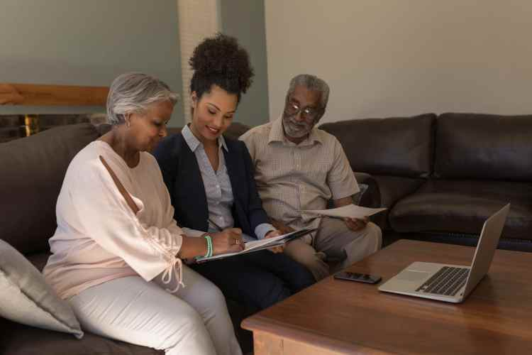 Woman signing property contract with real estate planning agent and senior man in living room at home