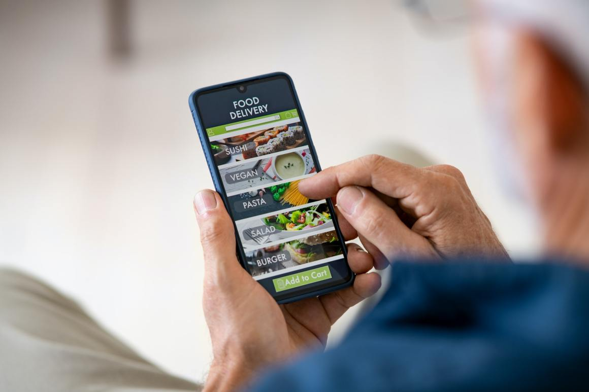Man using mobile app to order delivery food. Restaurant Apps Image