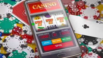 Online casino. Slot machine on smartphone screen, dice, casino chips and cards.