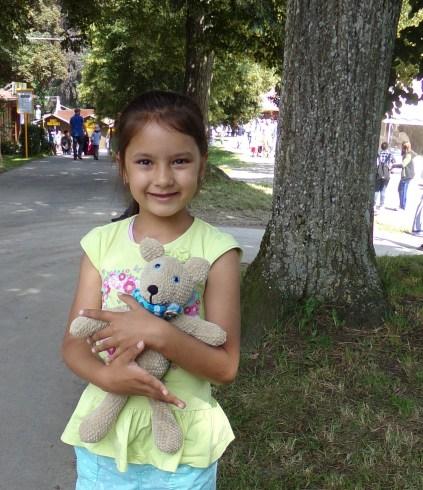 Na zdjęciu znajduje się stojąca obok drzewa dziewczynka w bluzce na krótki rękaw trzymająca piaskowego misia w niebieskim szaliku.