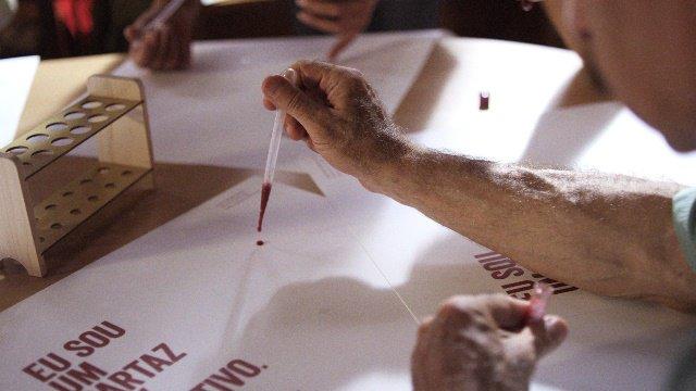 Confecção do cartaz com uma gota com sangue com HIV