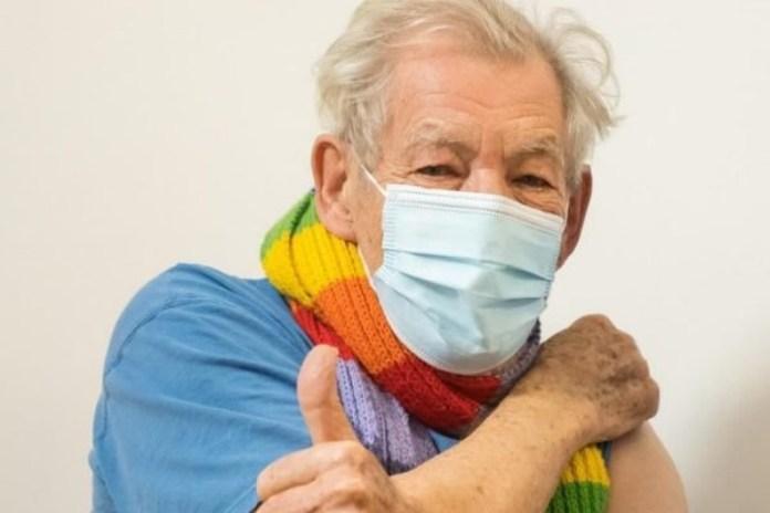 Ian McKellen se vacina contra o covid-19 com um cachecol do arco-íris