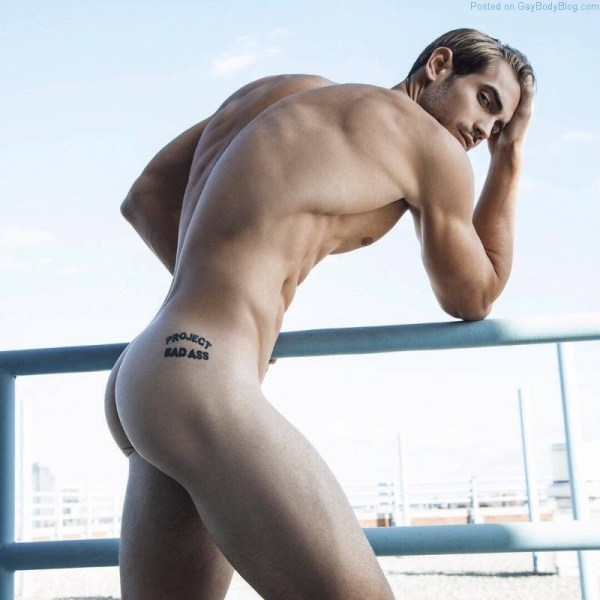 Modelo masculino Lucas Bloms pie desnudo exterior mostrando su culo y tatuaje