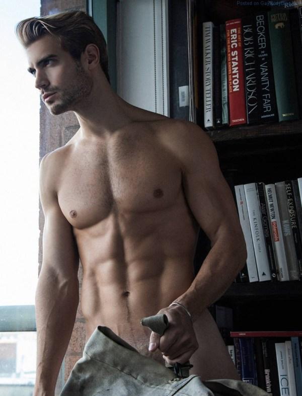Modelo masculino Lucas Bloms parado en una ventana sin camisa