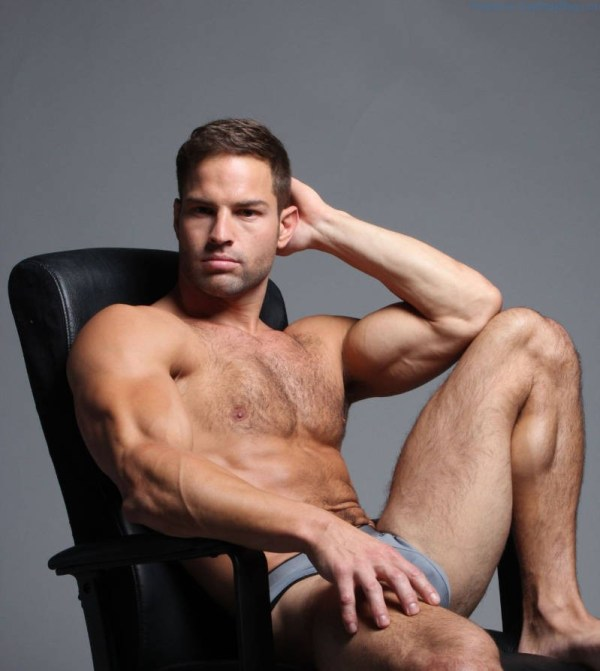 handsome and hairy hunk sitting back in a chair in just his underwear