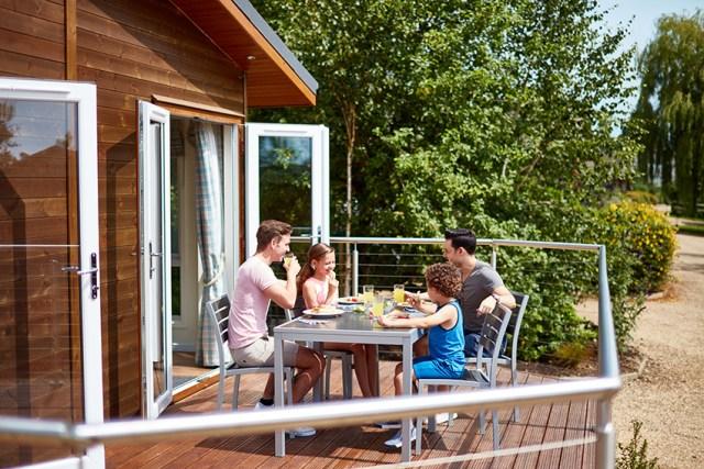 Gay family enjoying a meal on a Hoseasons lodge terrace.