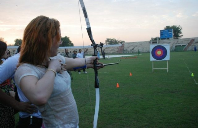 Woman drawing a bow and arrow pointed at an archery target