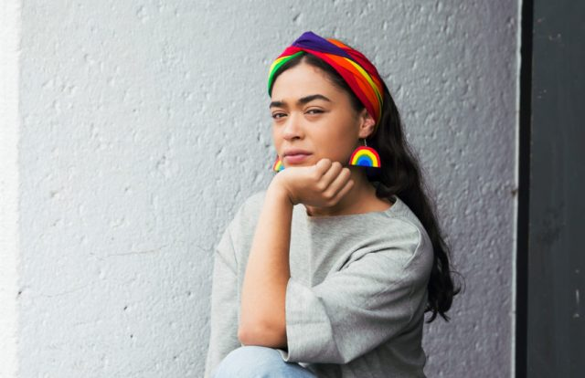 a woman with long brown hair is sitting on a step with her hand under her chin, she is wearing rainbow earrings