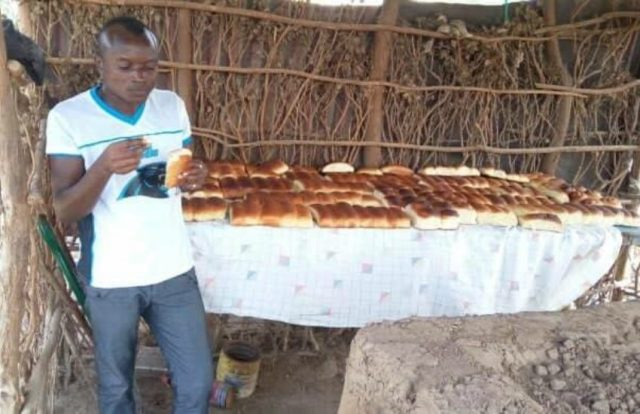 a man stands in front of a long table that is covered in loaves of bread