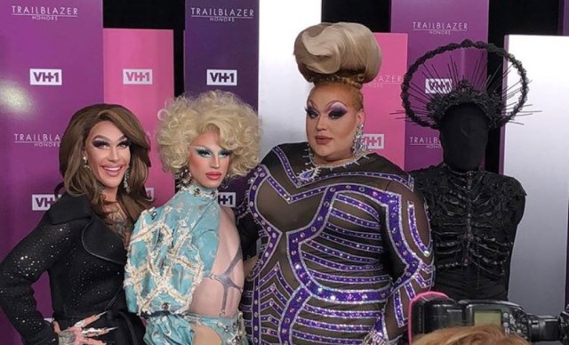 four drag queens posing on the red carpet.