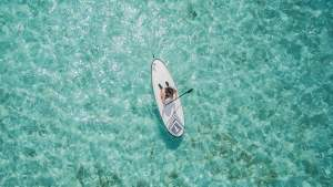Maldives water with paddle boarder.
