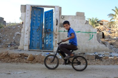 Kid on bicycle and a door to where once was a home full of life