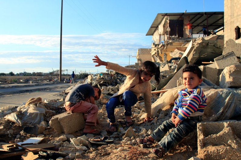 Kids playing by a ruined house