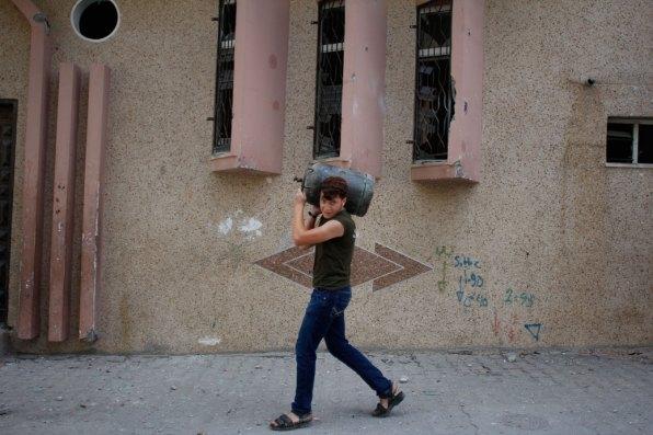 Boy carrying gas tank