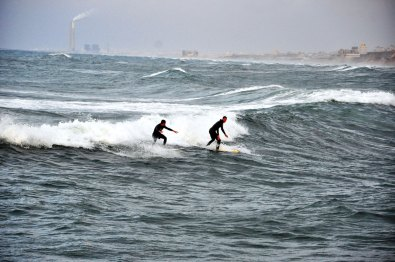 Surfers in the sea of Gaza; power plant is Israel.