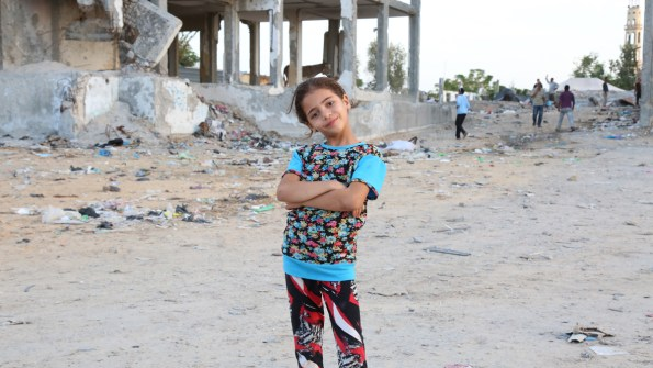 Girl poses with ruins behind her