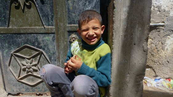 Boy squats by a door, Jabaliya refugee camp