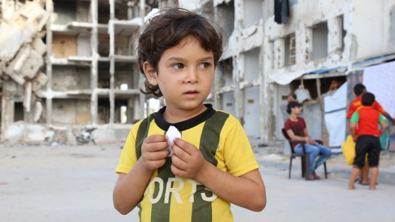 Boy with yellow soccer shirt with bombed building behind him