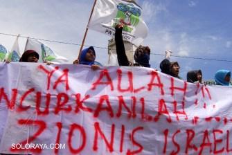 Aktivis yang tergabung dalam Kesatuan Aksi Mahasiswa Muslim Indonesia (KAMMI) Aceh, membentangkan spanduk saat menggelar aksi di kawasan Mesjid Raya Baiturrahman, Banda Aceh, Jumat (11/7).