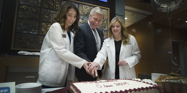 Two members of the School of Pharmacy's Class of 2019 cut the cake with Premier Dwight Ball.