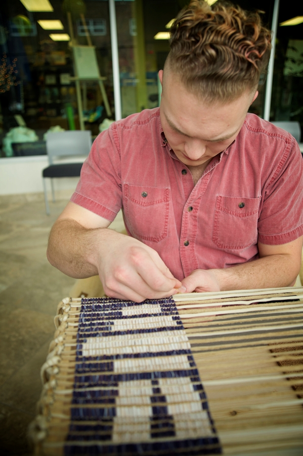 Visual arts student Dennis Wass works on an inuksuk design during the early stages of the wampum belt.