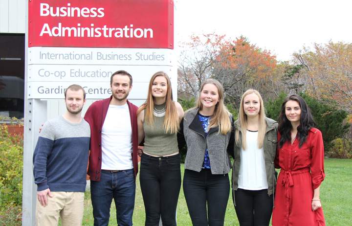 Students from the first Business Executive members of the first Business Administration Undergraduate Student Society post in front of the business building.