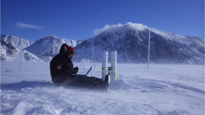 Dr. Trevor Bell programs a SmartSENSOR in the sea ice off Pond Inlet in May 2016. The buoy logs temperatures through the air, snow, ice and water, as a means to determine ice thickness, and transmits the information via satellite to the SmartICE operator. Behind the buoy is a manual sea-ice thickness station for validating the SmartSENSOR.