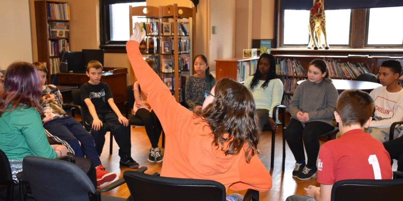 Schoolchikldren sit in a circle in the library at Bishop Feild School.