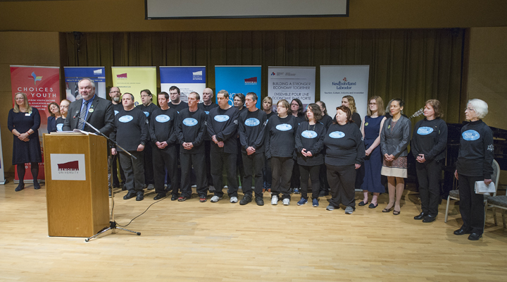 Dr. Wilfred Zerbe, at podium, introduces the Stella's Circle Inclusion Choir, who performed at the official launch of the Centre for Social Enterprise.