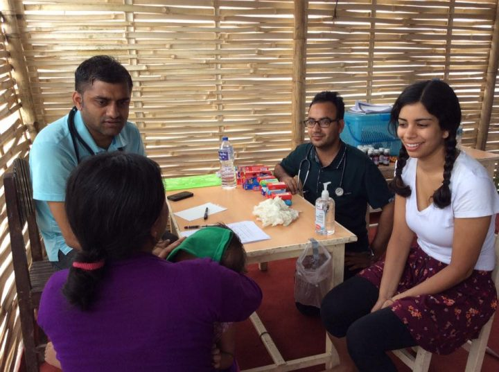 Medical students talk with a community member in the clinic