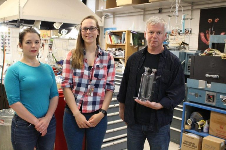 Sabrina Bélanger, Anke Krutof and Brian Power holding the distillation system for complex fluids he made for Dr. Kelly Hawboldt's research