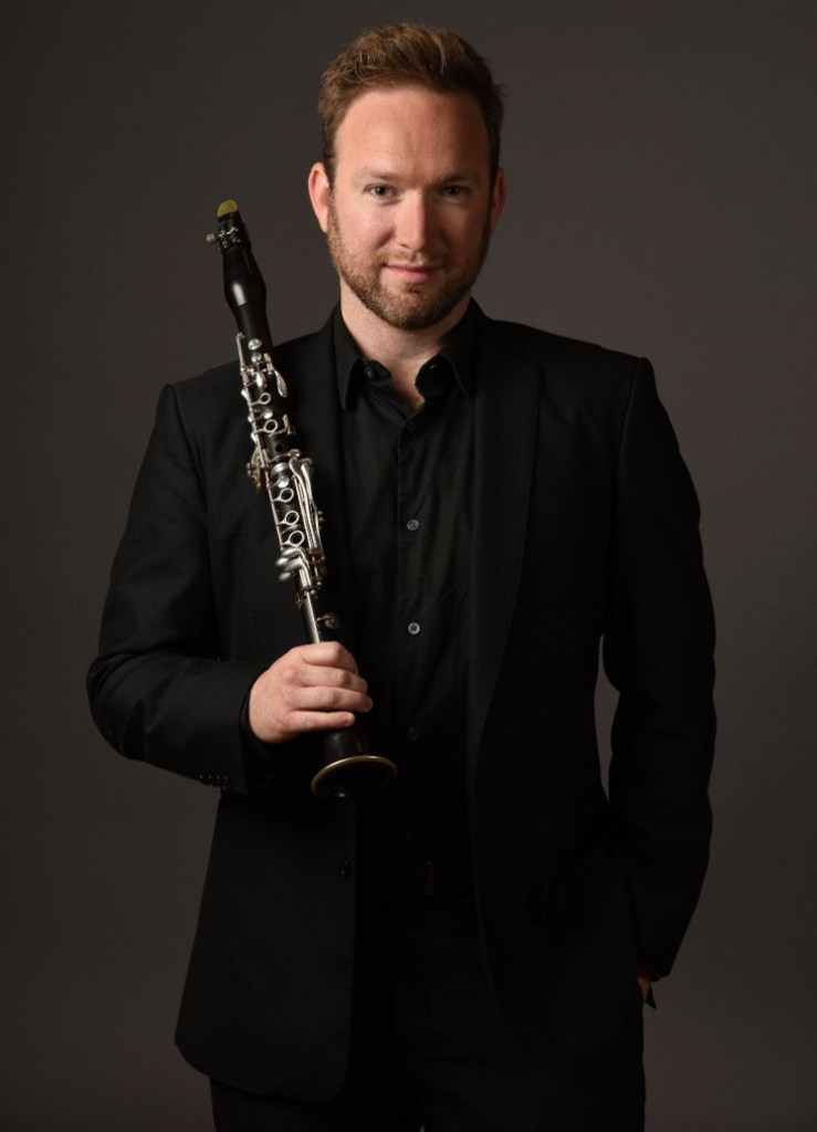Photot of man in suit holding a clarinet
