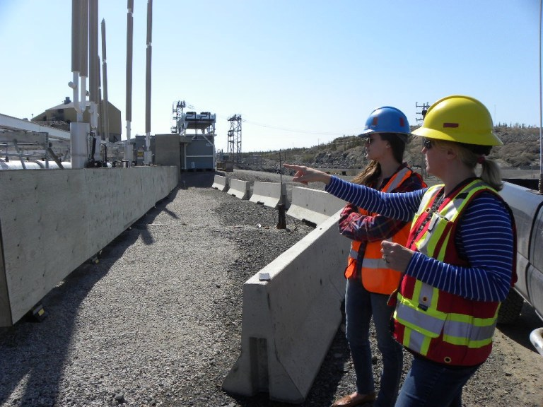 From left are Natalie Plato, Giant Mine remediation project team director, and Caitlynn Beckett pointing at the thermosyphons that keep arsenic frozen underground.