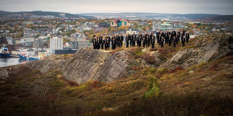 Group of boys dressed in black suits stand on rocks overlooking St. Johns Harbour