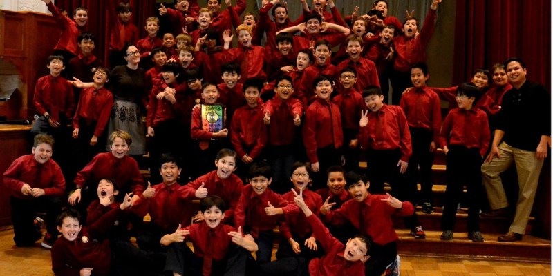 Group of young boys together pose for a photo, dressed in matching burgandy shirts and black pants, and looking excited.