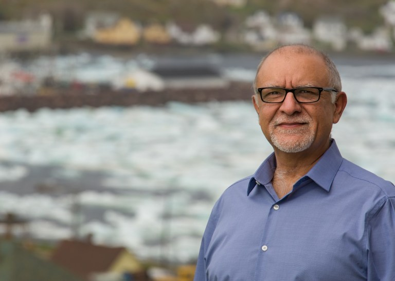 Man stands outside with ocean and community in background