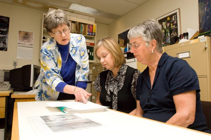 Three women looking over paper on a table