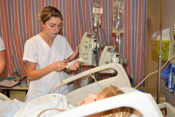 Female nursing student in white uniform administers IV medication on mannequin in nursing simulation room