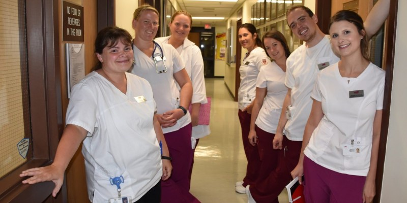 Dressed in white uniform tops with burgandy pants, a group of Nursing students stand with their professor in the hallway at Memorials Faculty of Nursing.