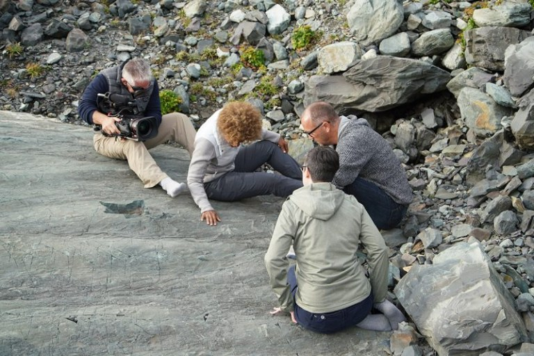 Show host Dr. Maydianne Andrade, University of Toronto, looks at Edicaran fossils at Mistaken Point, with Dr. Duncan McIlroy and Dr. Suzanne DuFour of Memorial University. Mike Grippo captures the moment in his socks – the fossil beds are 560 million years old, but remain delicate, so shoes are not permitted at the site.