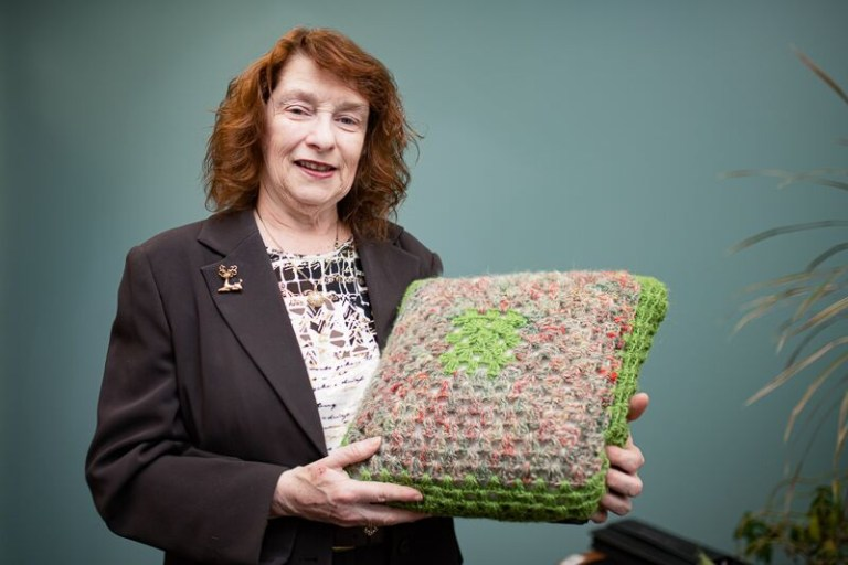 "Ann Browne with her ""N.L. Pillow."" The green wool is from an alpaca farm on the Port-au-Port peninsula. The mixture is from Baynoddy Farms in Chapel's Cove and the buttons are moose or caribou antler."