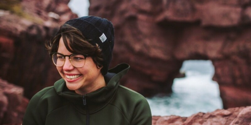 Photographer Alex Stead looks off camera while smiling and sitting against an ocean background of rocks and ocean.